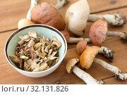 Купить «dried mushrooms in bowl on wooden background», фото № 32131826, снято 13 сентября 2018 г. (c) Syda Productions / Фотобанк Лори