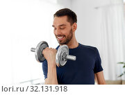 Купить «man exercising with dumbbell at home», фото № 32131918, снято 9 мая 2019 г. (c) Syda Productions / Фотобанк Лори