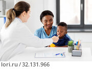 Купить «doctor examining african baby's mouth at clinic», фото № 32131966, снято 6 июня 2019 г. (c) Syda Productions / Фотобанк Лори