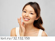 young asian woman applying moisturizer to her face. Стоковое фото, фотограф Syda Productions / Фотобанк Лори
