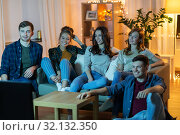 Купить «happy friends watching tv at home in evening», фото № 32132350, снято 22 декабря 2018 г. (c) Syda Productions / Фотобанк Лори