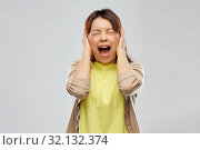 stressed asian woman closing ears and screaming. Стоковое фото, фотограф Syda Productions / Фотобанк Лори