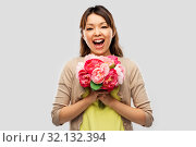 happy asian woman with bunch of flowers. Стоковое фото, фотограф Syda Productions / Фотобанк Лори