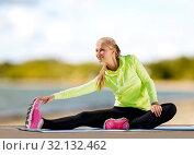Купить «woman stretching on exercise mat on beach», фото № 32132462, снято 19 июня 2013 г. (c) Syda Productions / Фотобанк Лори
