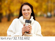 Купить «woman with hot drink in tumbler at autumn park», фото № 32132602, снято 13 октября 2018 г. (c) Syda Productions / Фотобанк Лори