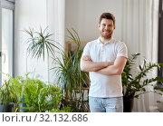 Купить «smiling man with houseplants at home», фото № 32132686, снято 22 мая 2019 г. (c) Syda Productions / Фотобанк Лори