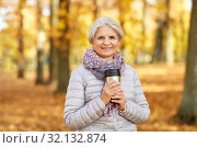 Купить «old woman with hot drink in tumbler at autumn park», фото № 32132874, снято 14 октября 2018 г. (c) Syda Productions / Фотобанк Лори