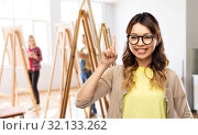 Купить «asian woman in glasses or student with finger up», фото № 32133262, снято 11 мая 2019 г. (c) Syda Productions / Фотобанк Лори