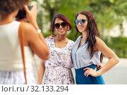Купить «woman photographing her friends in summer park», фото № 32133294, снято 22 июля 2018 г. (c) Syda Productions / Фотобанк Лори