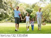 Купить «family with picnic basket walking in summer park», фото № 32133654, снято 30 июня 2019 г. (c) Syda Productions / Фотобанк Лори