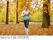 young woman running in autumn park. Стоковое фото, фотограф Syda Productions / Фотобанк Лори