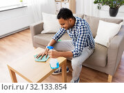 Купить «indian man cleaning table with detergent at home», фото № 32133854, снято 21 апреля 2019 г. (c) Syda Productions / Фотобанк Лори