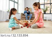 Купить «girls playing with toy crockery and teddy at home», фото № 32133894, снято 31 марта 2019 г. (c) Syda Productions / Фотобанк Лори