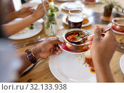 Купить «african man eating with friends at restaurant», фото № 32133938, снято 2 мая 2017 г. (c) Syda Productions / Фотобанк Лори