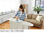 Купить «asian woman or housewife ironing bed linen at home», фото № 32134542, снято 13 апреля 2019 г. (c) Syda Productions / Фотобанк Лори