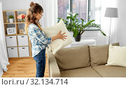 Купить «asian woman arranging sofa cushions at home», фото № 32134714, снято 13 апреля 2019 г. (c) Syda Productions / Фотобанк Лори