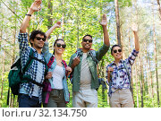 Купить «group of friends with backpacks hiking in forest», фото № 32134750, снято 15 июня 2019 г. (c) Syda Productions / Фотобанк Лори