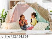 Купить «girls playing with torch in kids tent at home», фото № 32134854, снято 18 февраля 2018 г. (c) Syda Productions / Фотобанк Лори