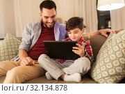father and son with tablet pc playing at home. Стоковое фото, фотограф Syda Productions / Фотобанк Лори