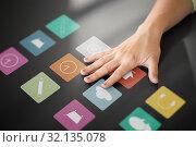Купить «hand using interactive panel with app icons on it», фото № 32135078, снято 31 мая 2018 г. (c) Syda Productions / Фотобанк Лори