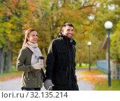 couple with tumbler walking along autumn park. Стоковое фото, фотограф Syda Productions / Фотобанк Лори