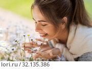 Купить «close up of woman smelling chamomile flowers», фото № 32135386, снято 12 июля 2019 г. (c) Syda Productions / Фотобанк Лори