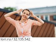 Купить «happy teenage girl with headphones in city», фото № 32135542, снято 20 июня 2019 г. (c) Syda Productions / Фотобанк Лори