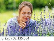 Купить «young woman smelling lavender flowers in garden», фото № 32135554, снято 12 июля 2019 г. (c) Syda Productions / Фотобанк Лори
