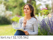 Купить «young woman writing to notebook at summer garden», фото № 32135562, снято 12 июля 2019 г. (c) Syda Productions / Фотобанк Лори