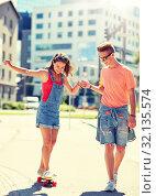 Купить «teenage couple riding skateboards on city street», фото № 32135574, снято 19 июля 2016 г. (c) Syda Productions / Фотобанк Лори