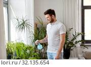 Купить «man spraying houseplants with water at home», фото № 32135654, снято 22 мая 2019 г. (c) Syda Productions / Фотобанк Лори