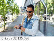 Купить «indian man with smart watch and backpack in city», фото № 32135686, снято 22 июня 2019 г. (c) Syda Productions / Фотобанк Лори