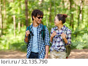 Купить «mixed race couple with backpacks hiking in forest», фото № 32135790, снято 15 июня 2019 г. (c) Syda Productions / Фотобанк Лори