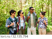 friends with backpacks on hike talking in forest. Стоковое фото, фотограф Syda Productions / Фотобанк Лори