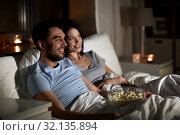 Купить «couple with popcorn watching tv at night at home», фото № 32135894, снято 27 января 2018 г. (c) Syda Productions / Фотобанк Лори