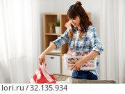 Купить «asian woman picking dirty laundry at home», фото № 32135934, снято 13 апреля 2019 г. (c) Syda Productions / Фотобанк Лори