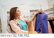 Купить «happy woman choosing clothes at clothing store», фото № 32136102, снято 19 февраля 2016 г. (c) Syda Productions / Фотобанк Лори