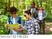 Купить «friends with map and backpacks hiking in forest», фото № 32136222, снято 15 июня 2019 г. (c) Syda Productions / Фотобанк Лори