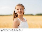 Купить «happy girl in headphones on cereal field in summer», фото № 32136254, снято 26 июля 2019 г. (c) Syda Productions / Фотобанк Лори