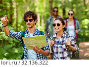 Купить «friends with map and backpacks hiking in forest», фото № 32136322, снято 15 июня 2019 г. (c) Syda Productions / Фотобанк Лори