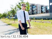 Купить «businessman with headphones riding scooter in city», фото № 32136494, снято 1 августа 2019 г. (c) Syda Productions / Фотобанк Лори