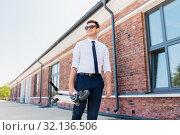 Купить «businessman with folding scooter on rooftop», фото № 32136506, снято 1 августа 2019 г. (c) Syda Productions / Фотобанк Лори