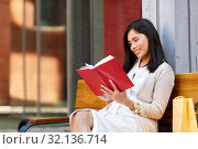 Купить «smiling asian woman reading book sitting on bench», фото № 32136714, снято 13 июля 2019 г. (c) Syda Productions / Фотобанк Лори