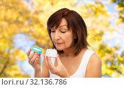 Купить «senior woman with cream jar over autumn trees», фото № 32136786, снято 8 февраля 2019 г. (c) Syda Productions / Фотобанк Лори