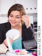 Купить «Office manager is making makeup before meeting», фото № 32140594, снято 21 мая 2017 г. (c) Яков Филимонов / Фотобанк Лори