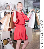 Купить «Young woman which is showing purchases in store», фото № 32140610, снято 27 мая 2017 г. (c) Яков Филимонов / Фотобанк Лори