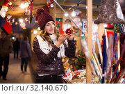 Купить «Ordinary young girl choosing xmas gifts at market», фото № 32140670, снято 22 декабря 2016 г. (c) Яков Филимонов / Фотобанк Лори