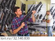 Купить «Adult cheerful man is choosing air-powered gun», фото № 32140830, снято 4 июля 2017 г. (c) Яков Филимонов / Фотобанк Лори