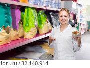 Купить «Glad shop assistant offers to choose pet food», фото № 32140914, снято 21 сентября 2019 г. (c) Яков Филимонов / Фотобанк Лори