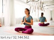 Купить «woman meditating in lotus pose at yoga studio», фото № 32144562, снято 21 июня 2018 г. (c) Syda Productions / Фотобанк Лори